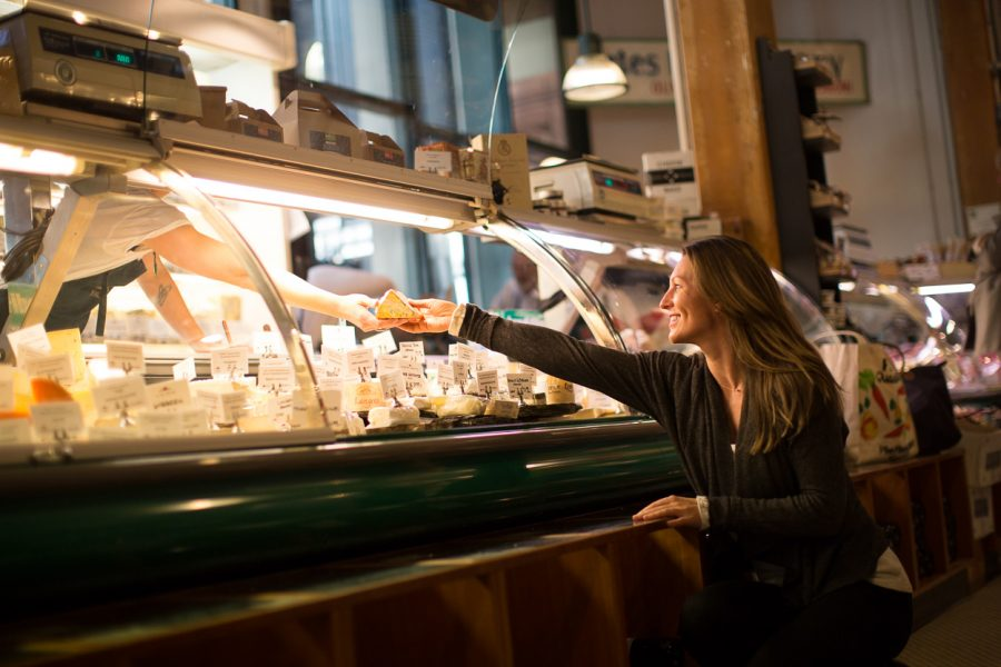 A woman reaching for cheese at the DeLaurenti cheese counter